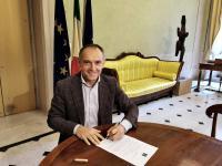 Foto del Presidente Luca Menesini seduto ad un tavolo che si appresta a firmare un documento